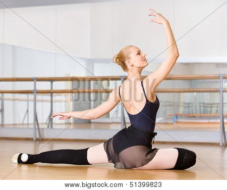 Ballerina does exercises sitting on the floor in the classroom with barre and mirrors