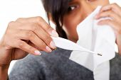 stock photo of viral infection  - Young sick woman checking her temperature  - JPG