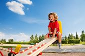 stock photo of seesaw  - Happy little three years old child riding seesaw with big smile and happy face - JPG