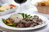 picture of gyro  - Gyro Doner garnished with rice Pilaf and vegetables partnered with hummus pita bread and red wine - JPG