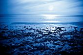 stock photo of moonlit  - The rising moon reflected in the ocean from a beautiful bay - JPG