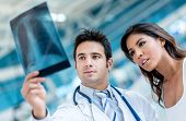 stock photo of physiotherapist  - Male doctor looking an x - JPG