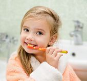 stock photo of white gown  - Smiling little girl brushing teeth in bath - JPG