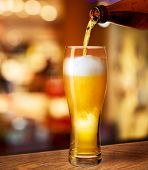 stock photo of beaker  - pouring beer in glass on bar or pub desk - JPG