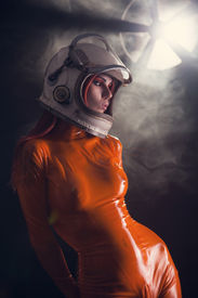 stock photo of fetish clothes  - Portrait of sexy girl in orange latex catsuit and space helmet - JPG