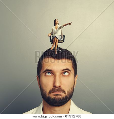 small serious woman sitting on the silly man and pointing at something