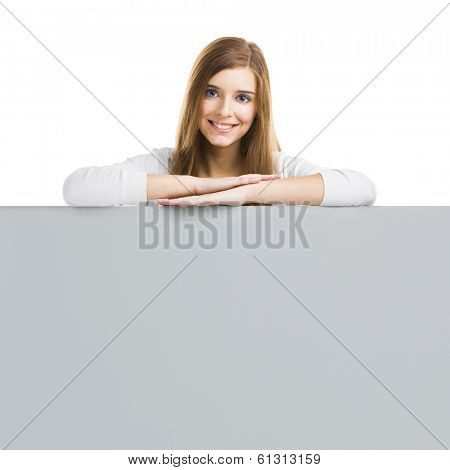 Young smiling woman leaning on a big blank board, isolated over white background