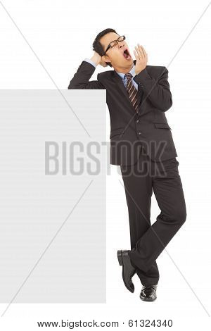 Businessman Yawning And Standing  With Blank Board