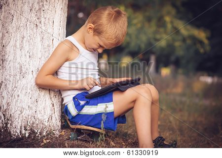 Boy Child Playing With Tablet Pc Outdoor With Summer Nature On Background Computer Game Dependence C