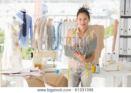 Portrait of a beautiful female fashion designer with folder in the studio