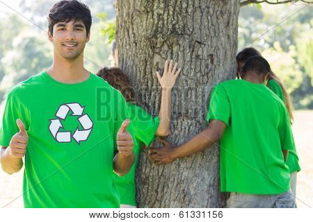 Portrait of confident male environmentalist gesturing thumbs up with friends hugging tree in background