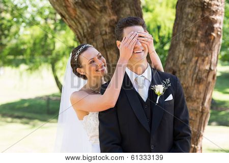 Happy young bride covering eyes of groom in garden