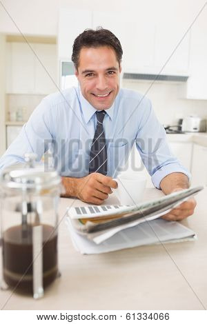 Portrait of a smiling well dressed man with coffee cup and newspaper in the kitchen at home
