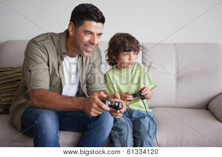 Cheerful father and son playing video games in the living room at home