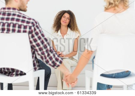 Therapist smiling at reconciled couple holding hands at therapy session