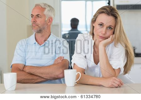 Fed up woman sitting at the counter with her partner at home in the kitchen