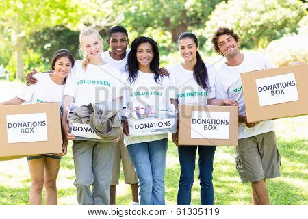 Group portrait of happy volunteers carrying donation boxes in park