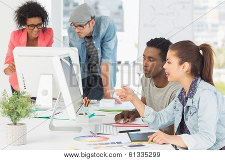 Group of casual artists working at desk in the creative office