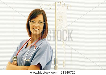 Happy Nurse With Iv Stand In Front Of Window