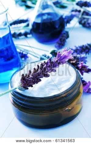 a cream jar and some lavender flowers and flasks in a cosmetics laboratory