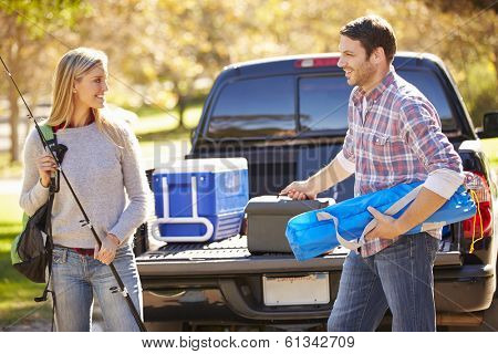 Couple Unpacking Pick Up Truck On Camping Holiday