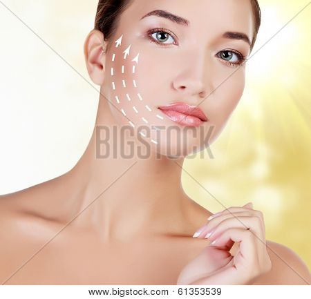 Young female with clean fresh skin, abstract background with blurred lights
