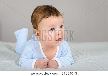 Cute Smiling Baby Boy In Bed Lying On His Belly In Bedroom