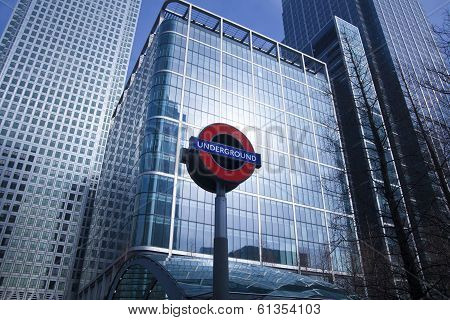 LONDON, UK - MARCH 10, 2014: Canary Wharf skyscrapers and tube station sign. Every day tube bringing