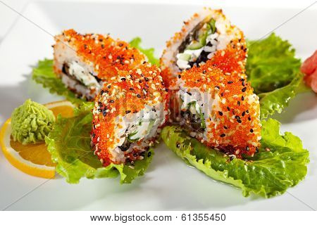 Maki Sushi with Smoked Eel, Fresh Cucumber, Salad Leaf, Cream Cheese and Prawn inside. Tobiko (flying fish roe) and Sesame outside