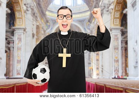 Male reverend holding a football and cheering in a church