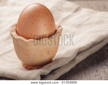 Brown Egg In Handmade Holder On Rustic Table