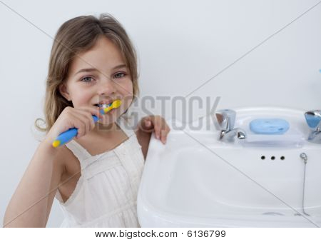 Portrait Of A Little Girl Cleaning Her Teeth