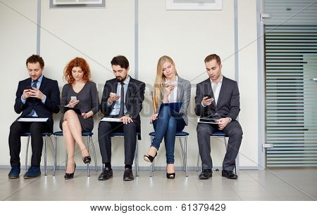Row of several business partners using their mobile phones
