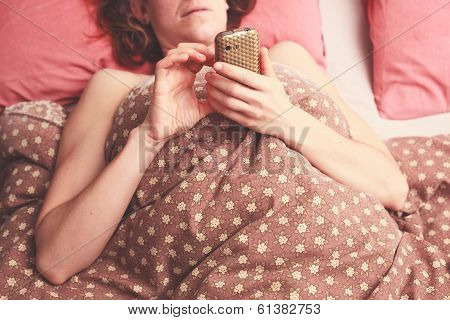 Young Woman Texting In Bed
