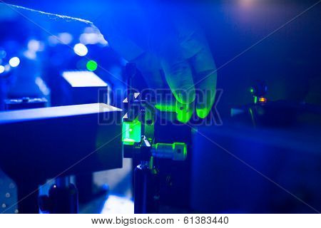 Quantum optics - hand of a researcher adjusting a laser beam in a lab