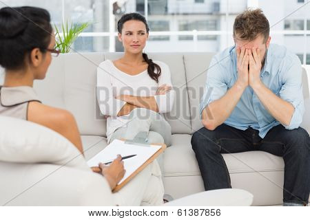 Unhappy couple sitting on sofa at therapy session in therapists office