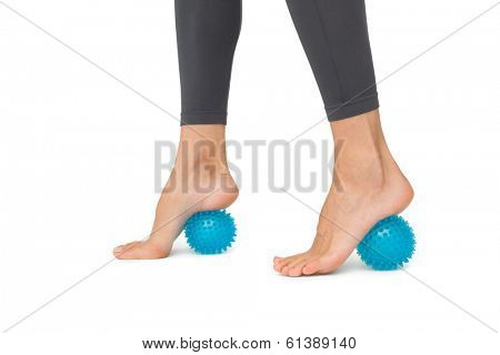 Close-up low section of woman standing over stress ball against white background