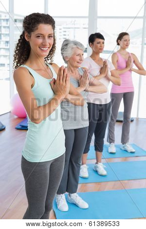 Happy female trainer with class standing in namaste pose at yoga class