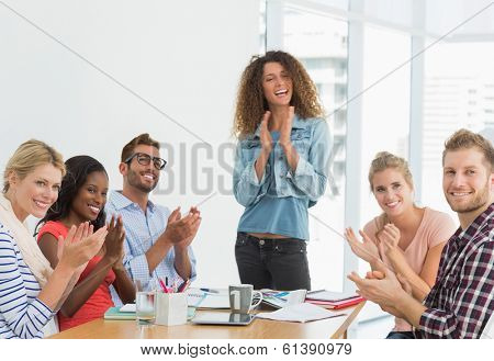 Team of designers applauding at the camera in creative office