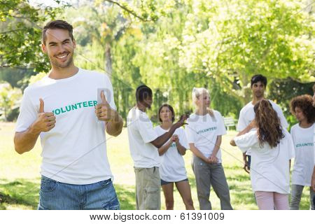 Portrait of handsome volunteer showing thumbs up with friends disucssing in background