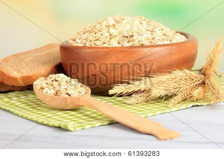 Composition with raw oat-flakes in bowl  and fresh bread slices, on wooden table, on bright