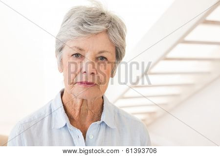 Retired woman frowning at the camera at home in living room