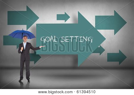 The word goal setting and peaceful businessman holding blue umbrella against blue arrows pointing