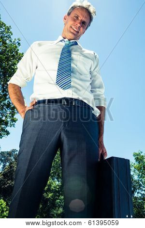 Low angle portrait of confident businessman carrying briefcase against clue sky