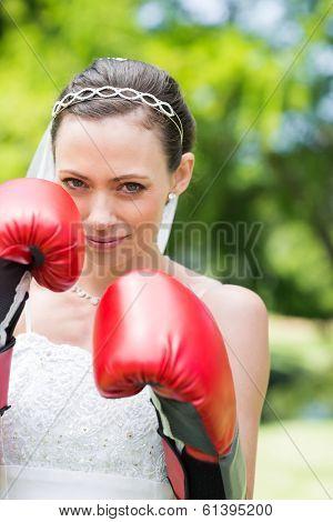 Portrait of woman in wedding dress wearing boxing gloves in park