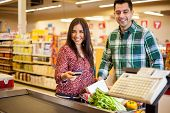 stock photo of cash register  - Beautiful young woman and her partner paying for groceries at the cash register with a credit card