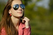 beautiful girl with sunglasses in dandelion field