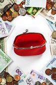 Foreign coins and banknotes frame with red purse. Money background