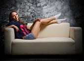 Young girl on sofa at grey wall