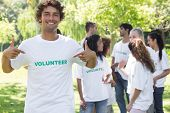 stock photo of environment-friendly  - Portrait of male volunteer pointing at tshirt with friends in background - JPG